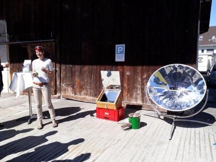 Petra Bolfing präsentiert drei Kocher, vlnr: Solarkocher, engergiespar Holzkocher, Parabolspiegelkocher